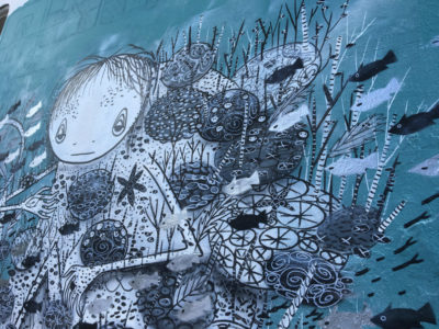 graffiti drawing of girl in the blue sea with fish