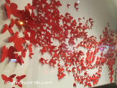 red paper butterflies flooding across a wall in collingwood