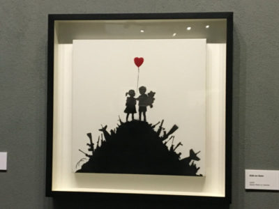 girl and boy holding a heart shaped balloon on a pile of guns