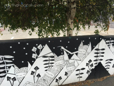 black and white graphical street art and greenery