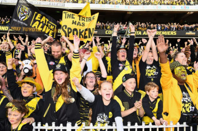 young and old richmond supporters waving flags and banners at a football game