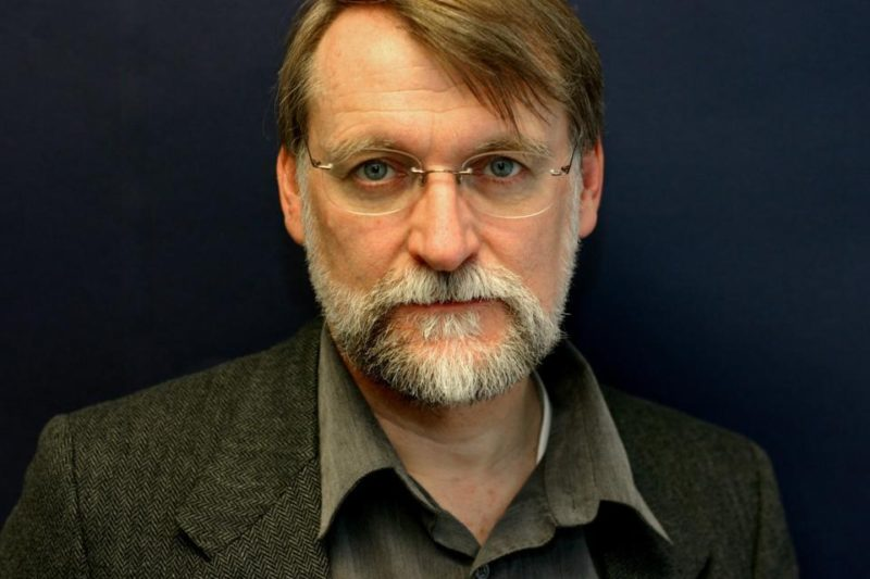 picture of man in brown suit with glasses looking at the camera
