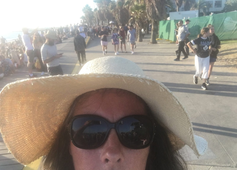 people beyond on a boardwalk at the beach at st kilda festival with pipeldoot in the front in a hat and sunglasses