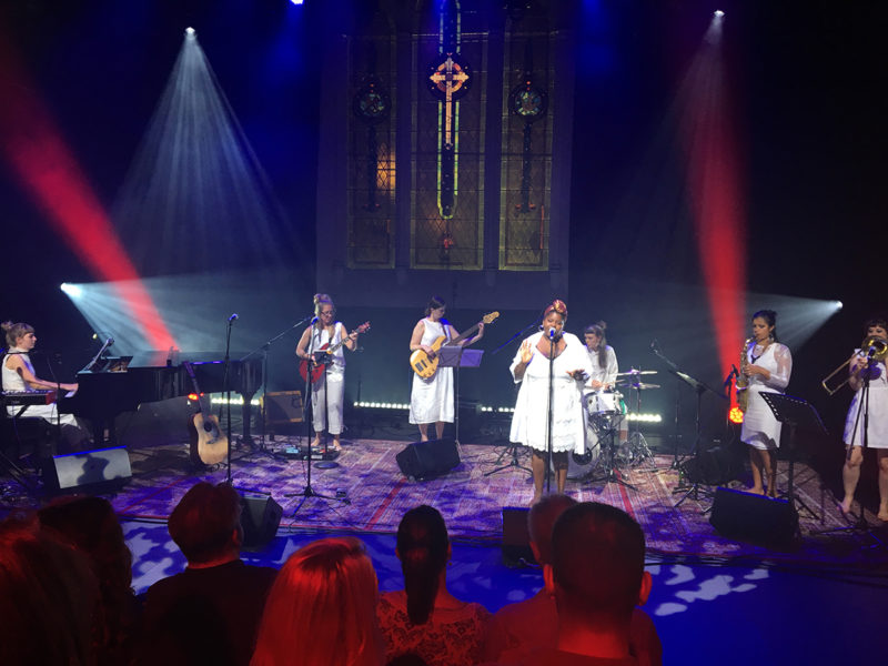 stage bathed in blue and red light filled with women wearing white and playing music - for thando summer sessions